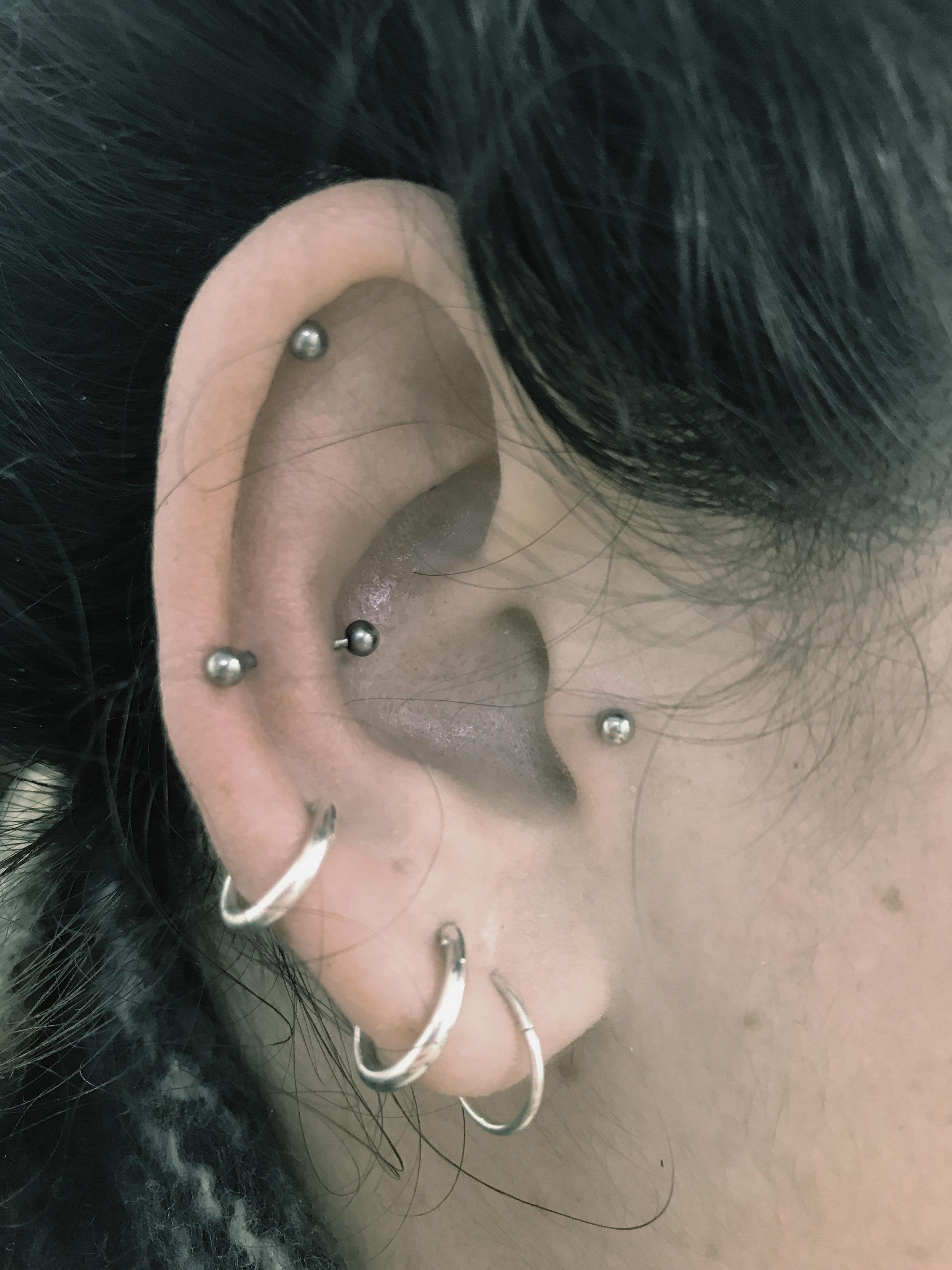 Cute little snug piercing along side a Tragus piercing & a high Helix piercing