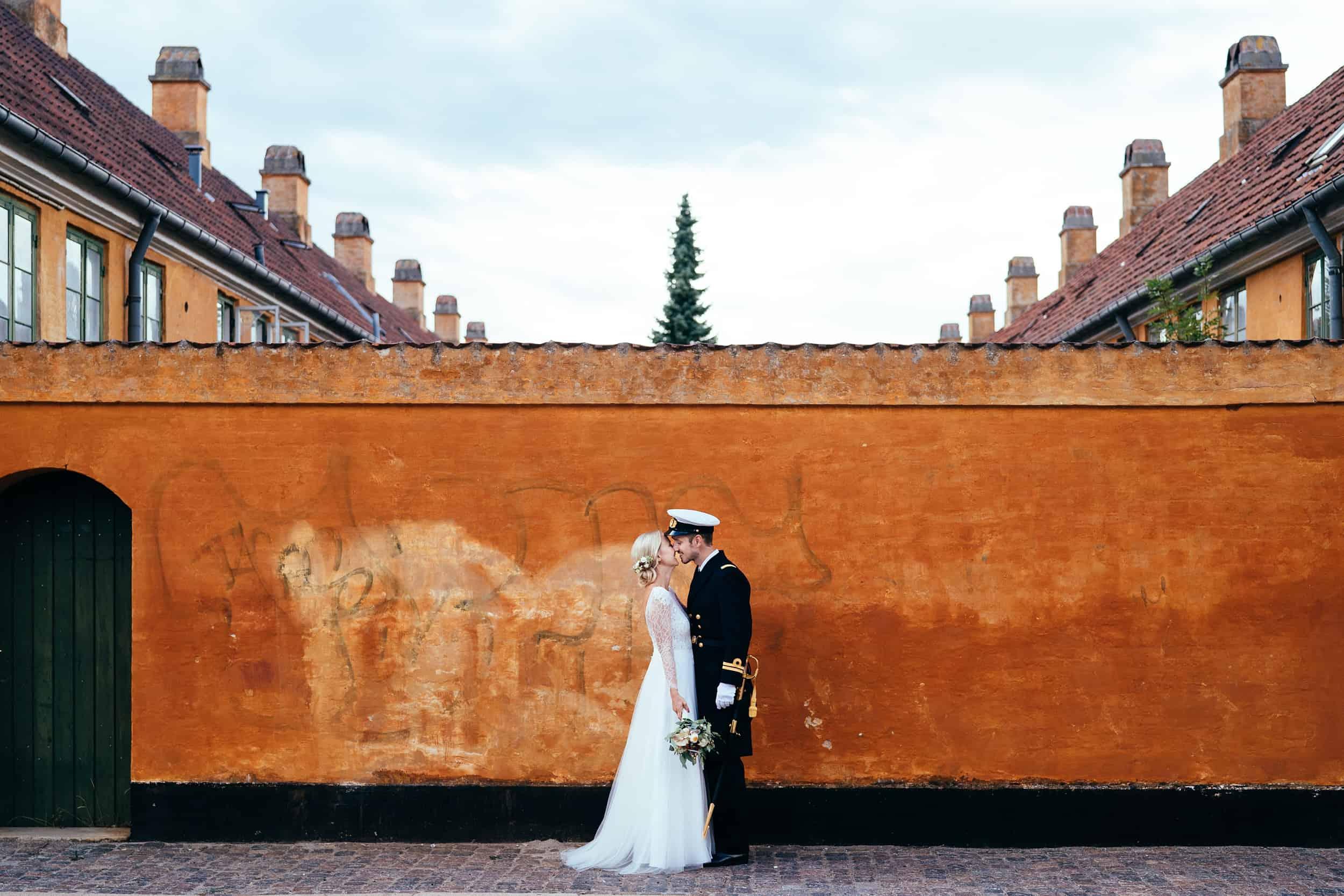 brudepar-ved-orange-væg.jpg