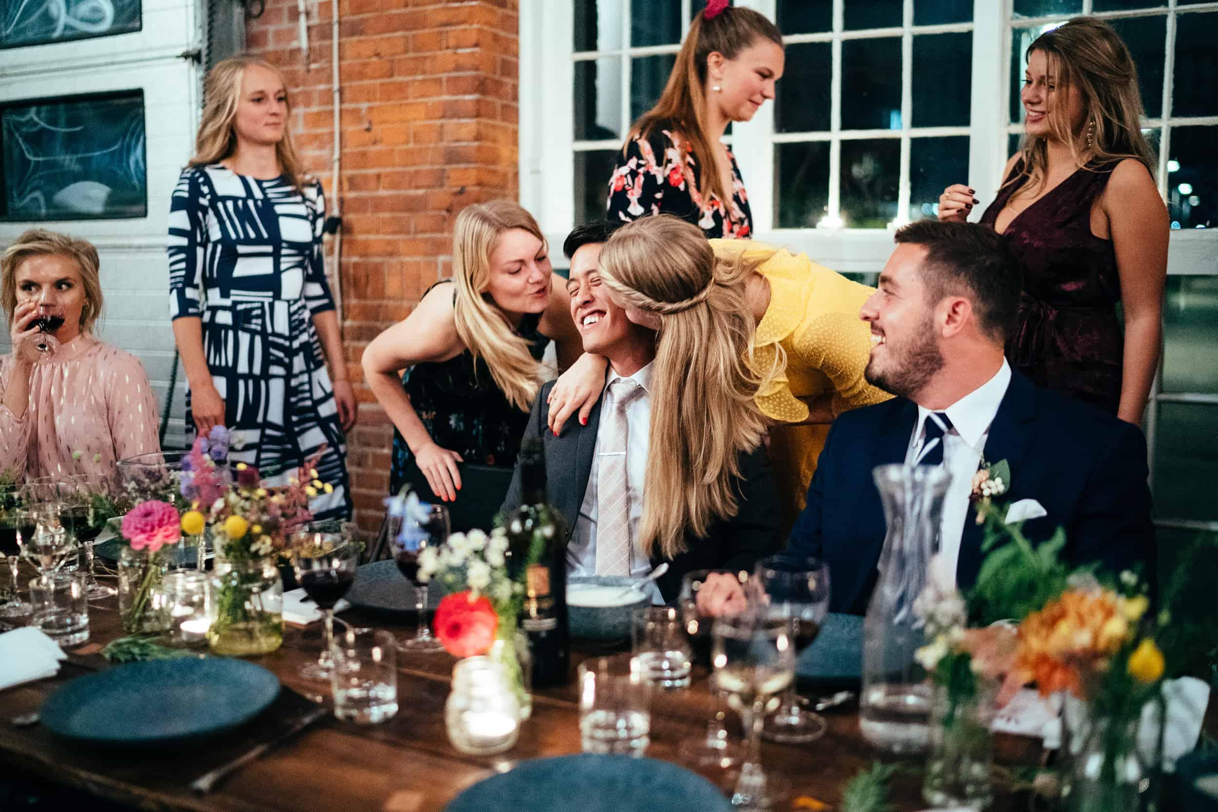 brudgom-bliver-kysset-af-bryllupsgæster.jpg