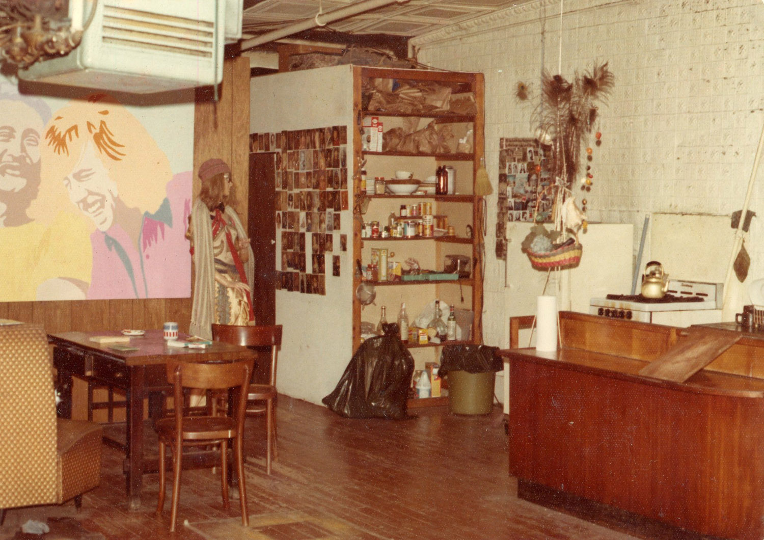 The dining area and kitchen, c. 1972.  Carla's painting of David Crosby and Graham Nash from Crosby Stills Nash and Young seen on wall.