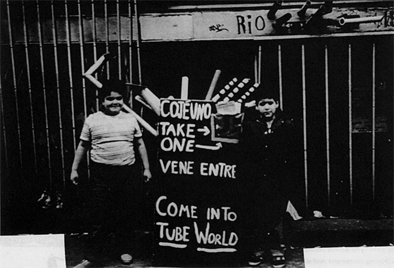 Local children Maria Acosta and friend stand by the Tube World signboard in front of No Rio, 1982. Photo by Jody Culkin