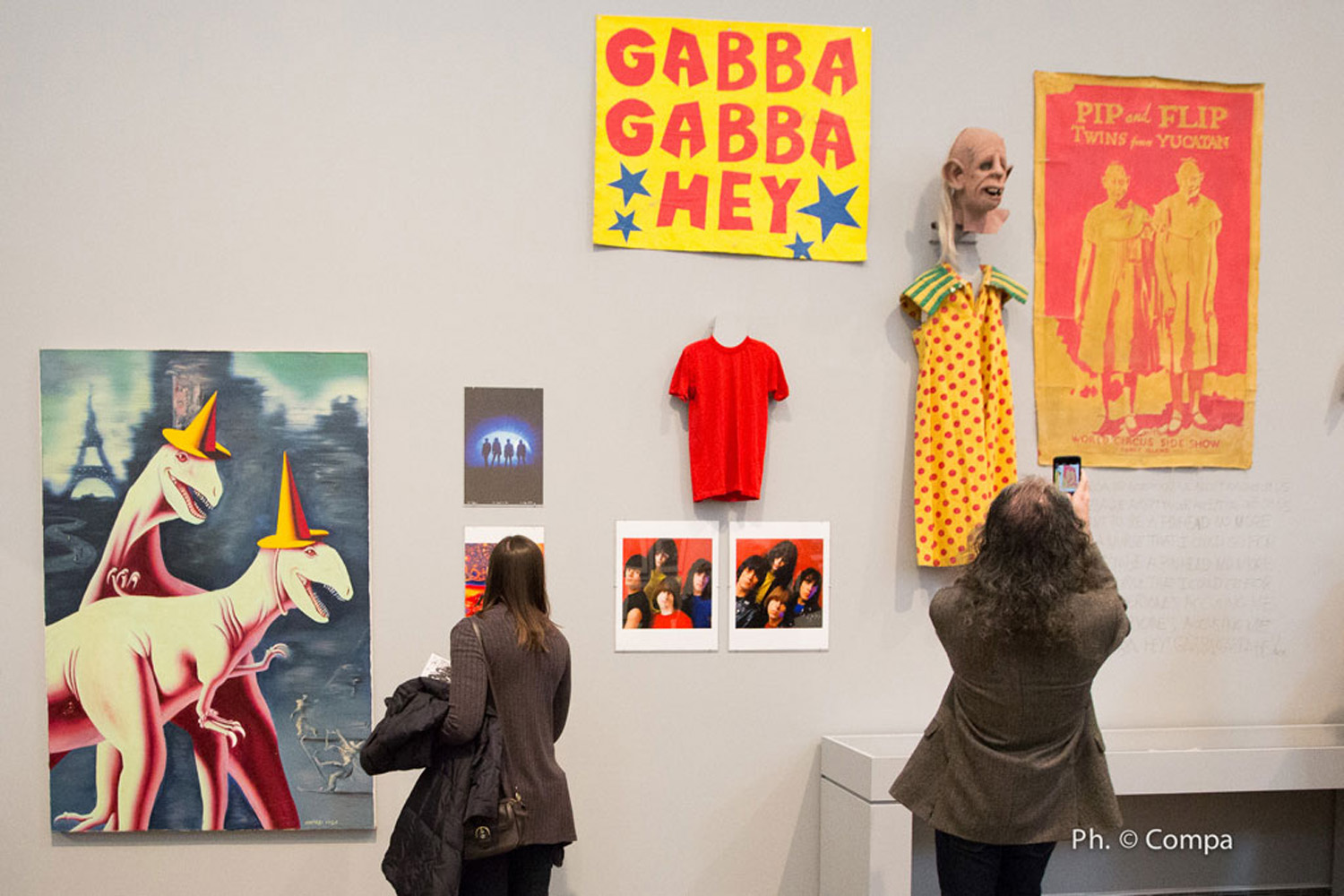 "Left to right: Mark Kostabi's painting ""Enasaurs"" (used as the cover for the Ramones' album ¡Adios Amigos!); George DuBose's photographs of the Ramones; End of the Century album cover and outtake by Mick Rock; t-shirt worn by Johnny Ramone on the cover for the album End of the Century; ""Gabba Gabba Hey"" sign and ""Pinhead"" mask and dress used onstage by the Ramones; Bobby Belfiore's painting ""Pip and Flip"" (from the nightclub Coney Island High). Photo by Andrea Compa."