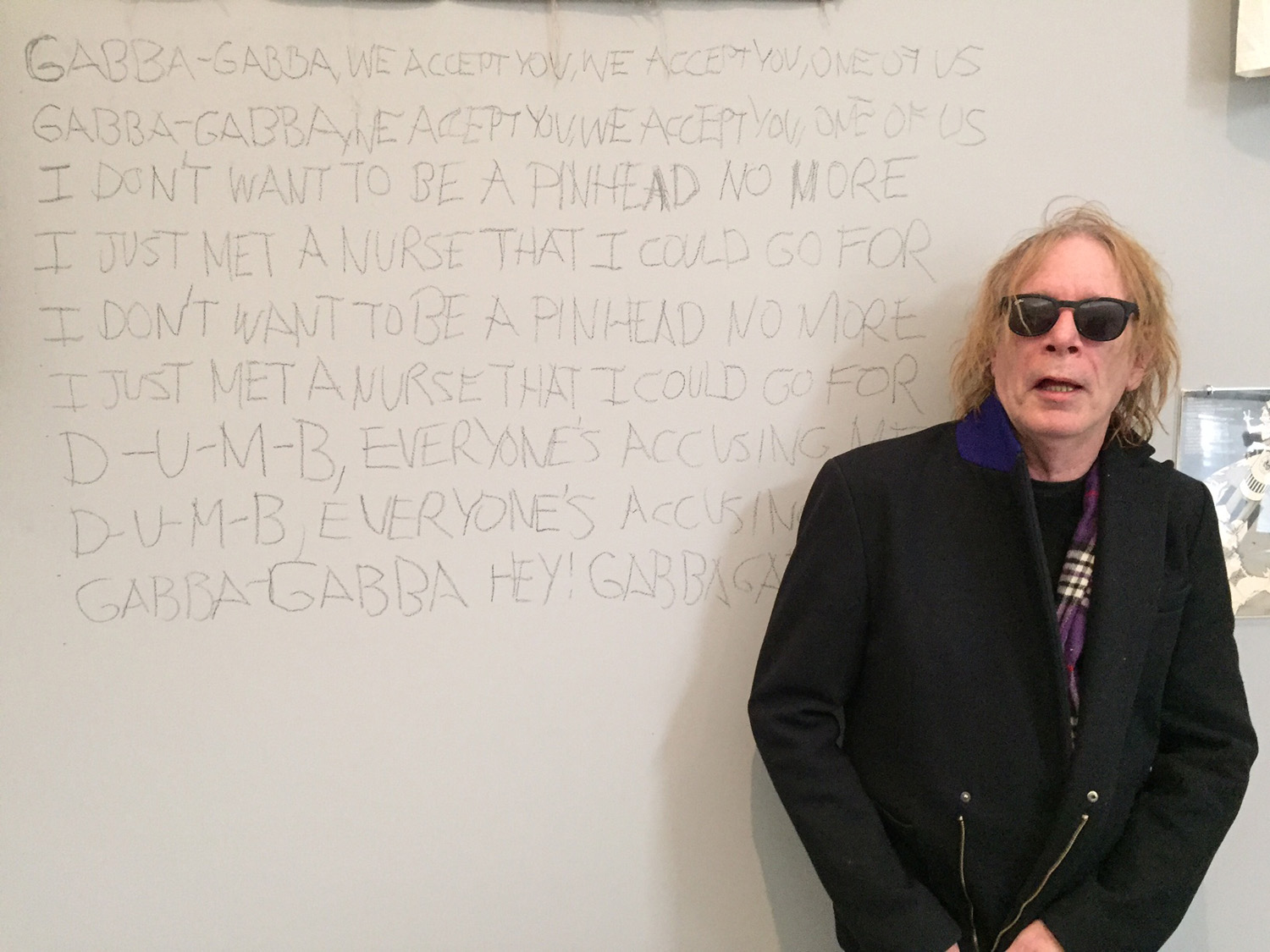 "Punk magazine co-founder and ""resident punk"" Legs McNeil with the lyrics to the Ramones' song ""Pinhead,"" which he scrawled onto the wall of the Queens Museum. Photo by Pema Domingo-Barker."
