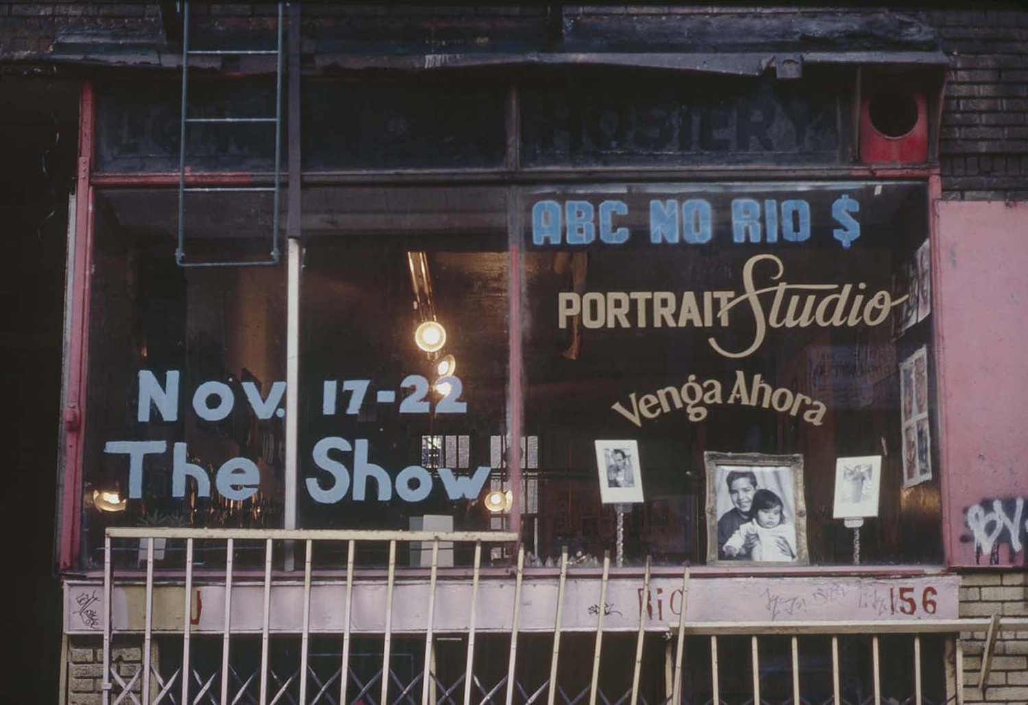 Exterior of No Rio during the portrait show showing letters painted on the window by Ilona Granet. Photo by Tom Warren