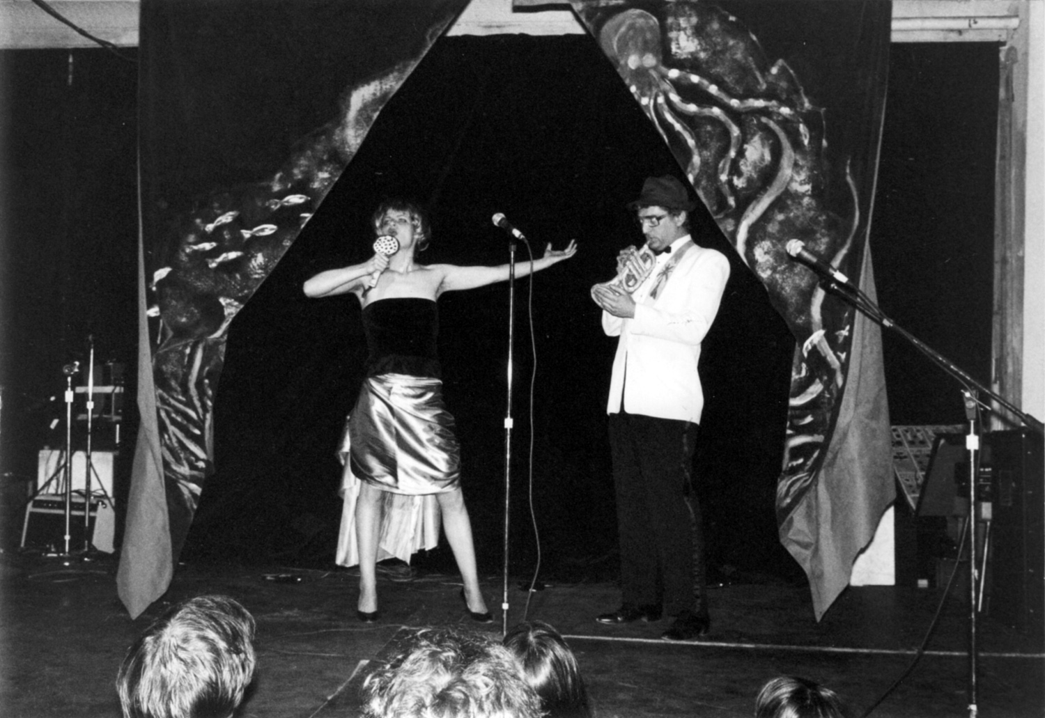 "No Rio's Cardboad Air Band at the Island of Negative Utopia: Bebe Smith belts out a song as Walter Robinson ""plays"" trumpet. Photo by Teri Slotkin"