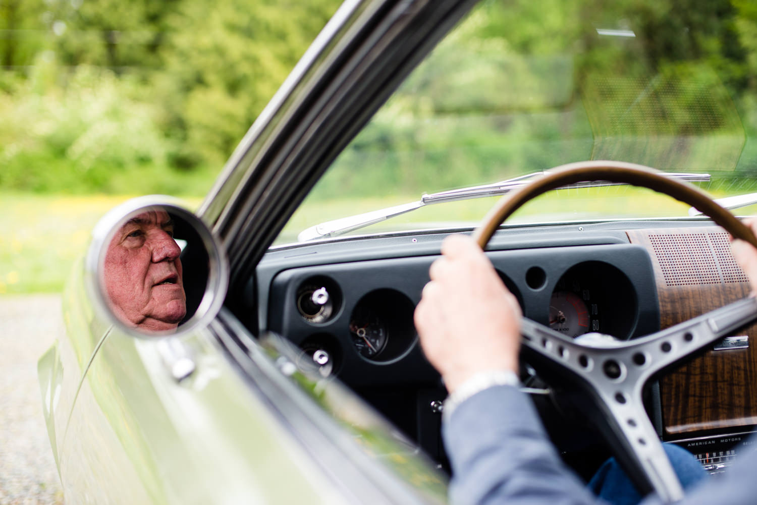 octogenarian man driving vintage car