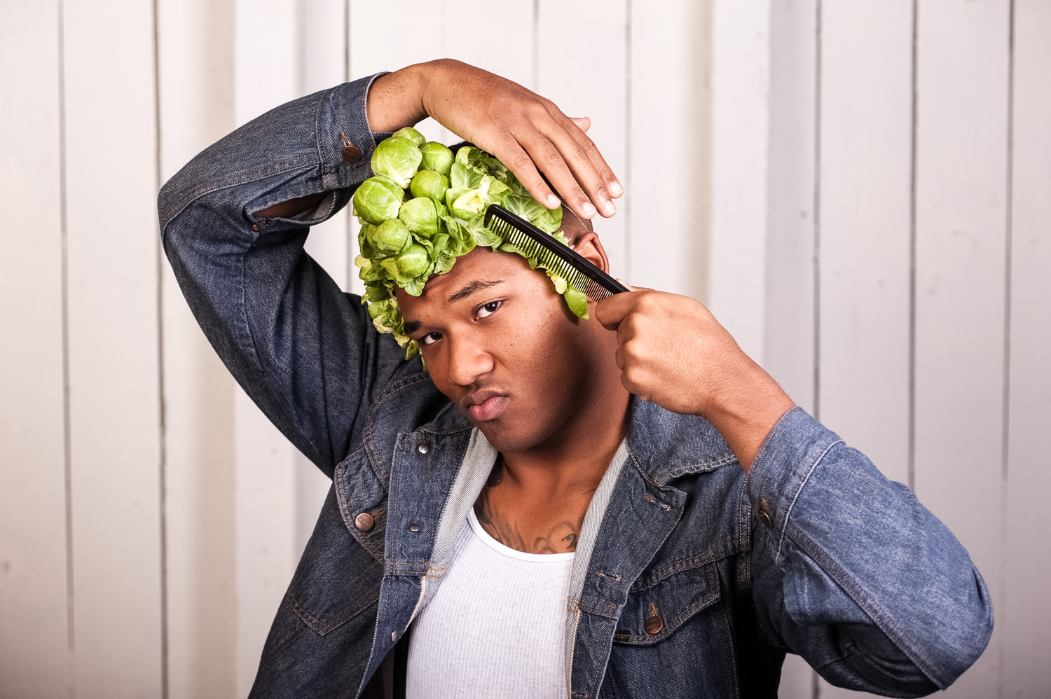 man combing fake hair with brussel sprouts