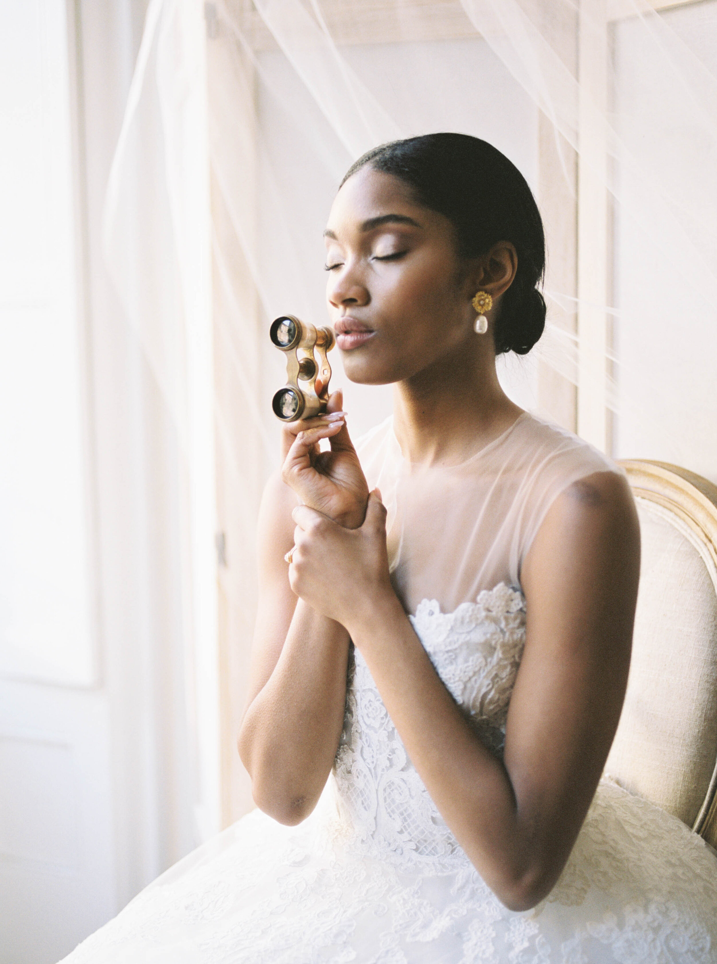 New York City Bridal Editorial featuring Reem Acra wedding gown and monochrome white bouquet with opera glasses by Liz Andolina