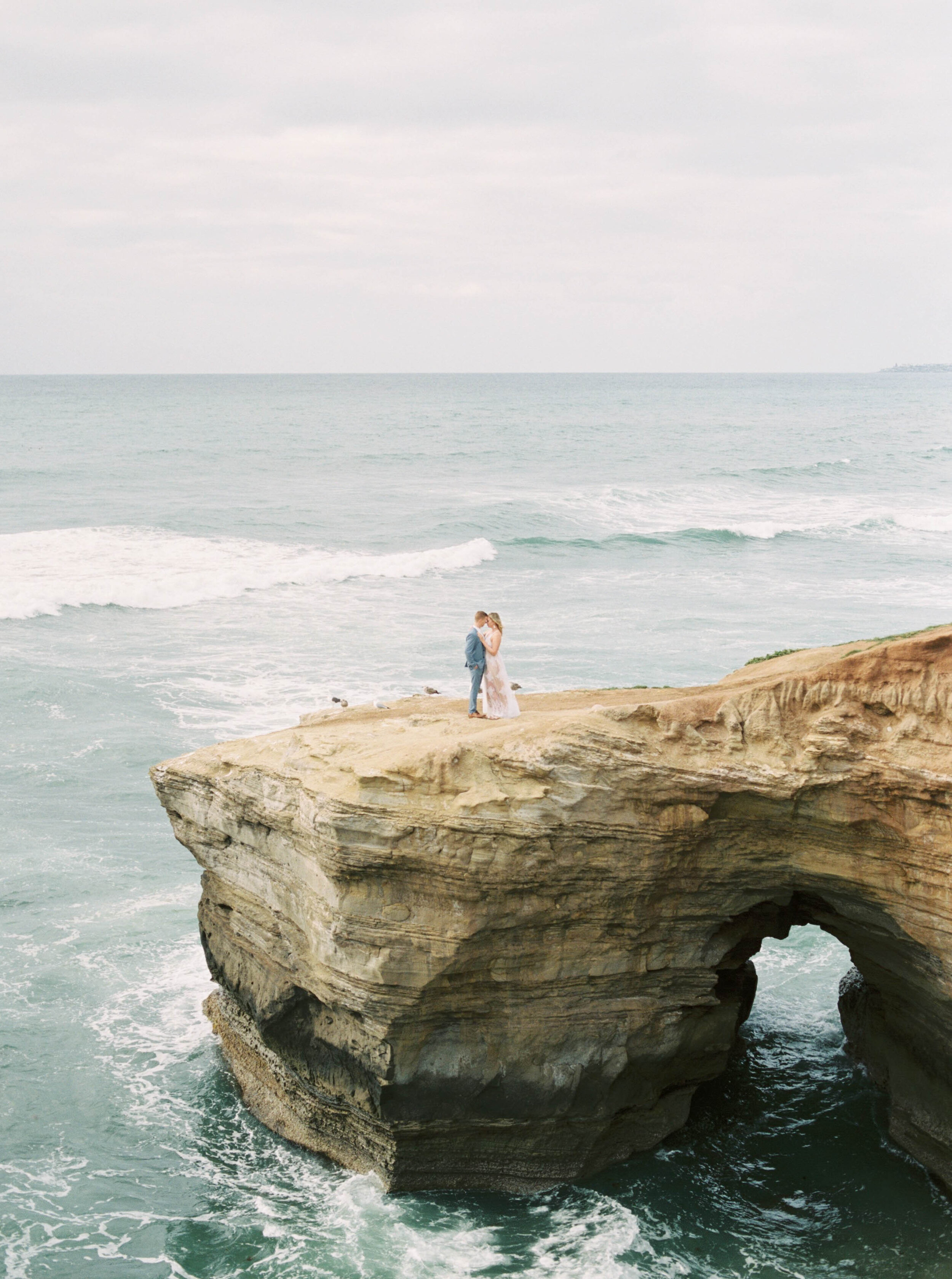 Anniversary wedding session on film at the Sunset Cliffs in San Diego California with stylish white flowy dress and blue suit by the ocean and beach by Liz Andolina Photography