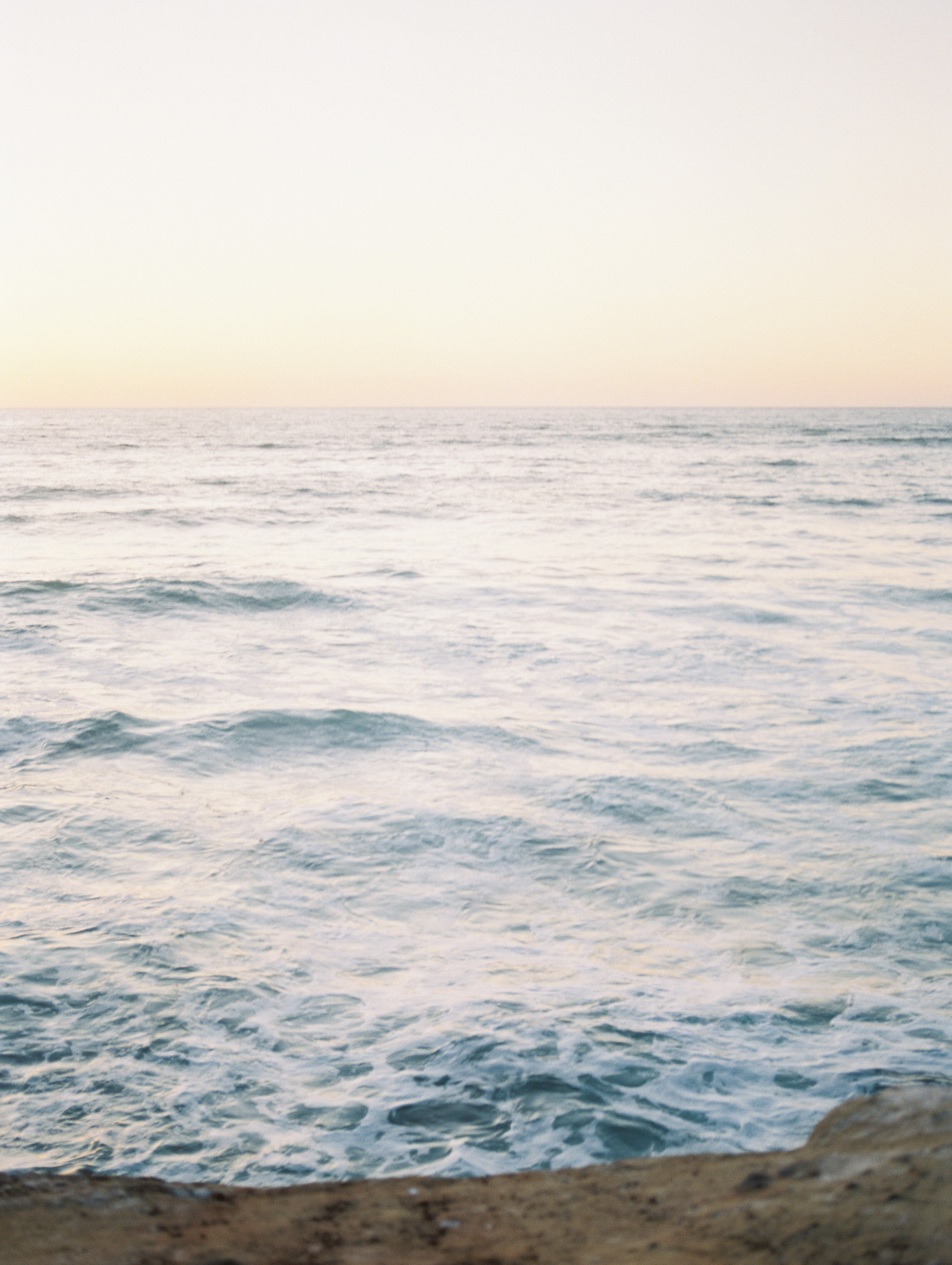 Elegant ocean inspired wedding with blue wedding dress and white tux on film at the Sunset Cliffs in San Diego California by Liz Andolina Photography