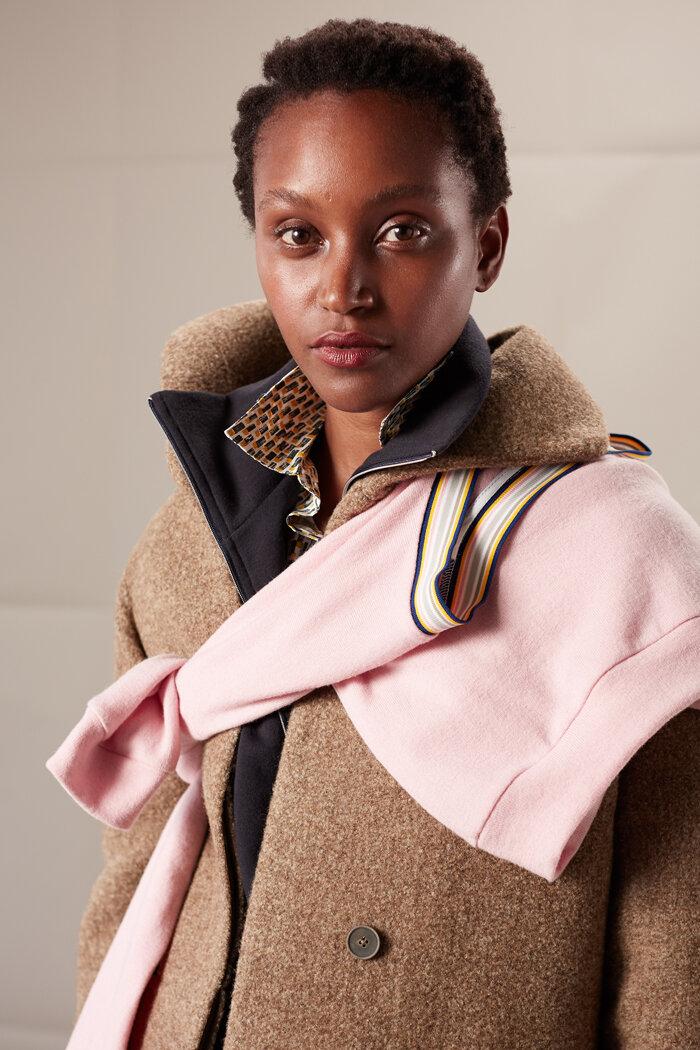 Federleichter cappucinofarbener Mantel aus Lamahaar kombiniert mit rosa V-Pullover mit Ringelstrickbündchen