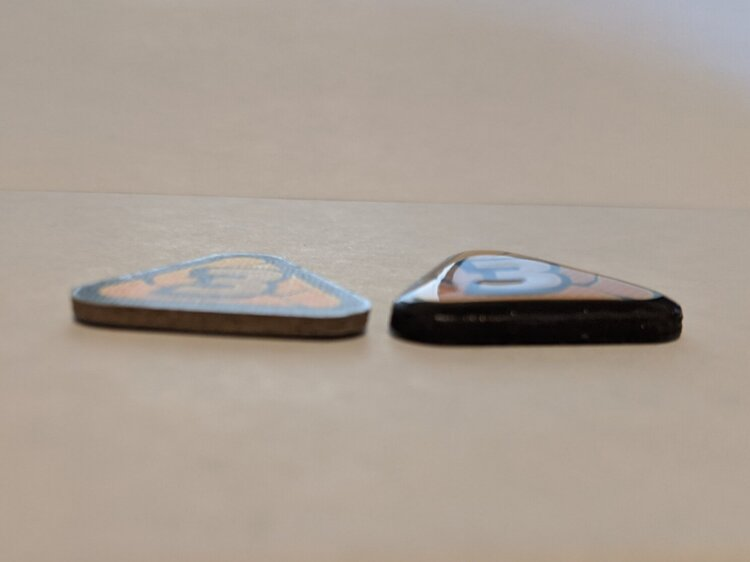 Left, sad plain token. Right, happy glossy token