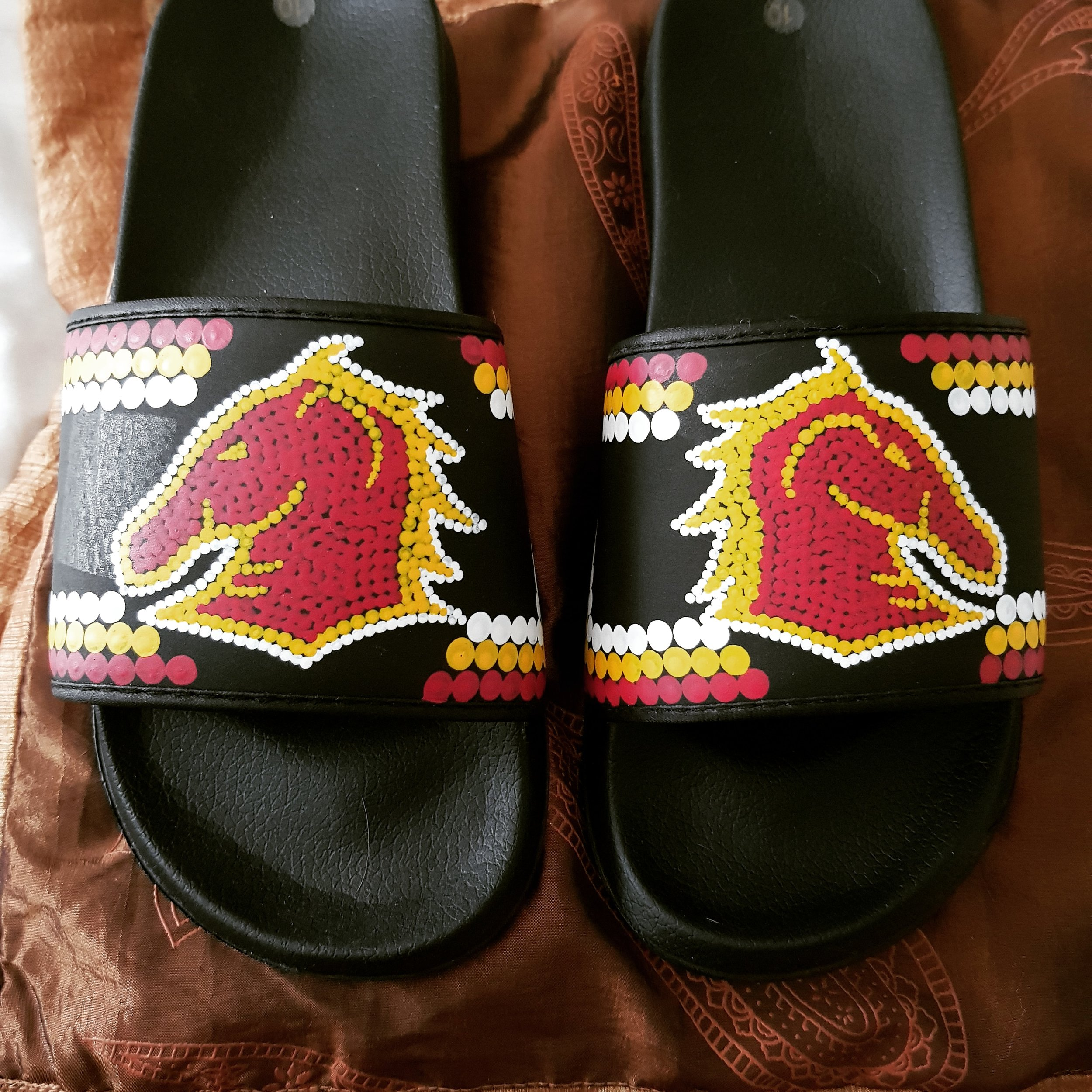 CREED DESIGNS - MINELLE46@OUTLOOK.COMMinelle Creed is an Aboriginal woman descended from the Kalkadoon and Gunggari peoples in Queensland. In her spare time, Minelle has taken up painting, arts and crafts. Minelle likes to paint contemporary Aboriginal designs on shoes, handbags and guitars. Minelle also likes creating jewellery using emu feathers, crystals or glass beads and native seeds.