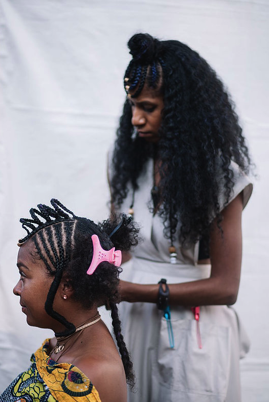 TAMARA ALBERTINI - While traditional African braiding styles are a popular phenomenon that continues to be modified and unfortunately appropriated, very few fully understand the importance of the tradition nor possess the knowledge on what makes these styles so special. Haitian hair specialist Tamara Albertini is here to shift the narrative through education on the history of traditional African hair braiding with her mobile salon, Ancestral Strands. Whether through Tigray-inspired plaits, Fulani-style corn rows, or Gilbich braids, Tamara explains the fascinating history behind each style to give her client a deeper understanding of their choice. Tamara offers her clients more than just beautifully intricate coiffures, but is also a holistic specialist providing her clients with personalized herbal hair care treatment using ancient practices.