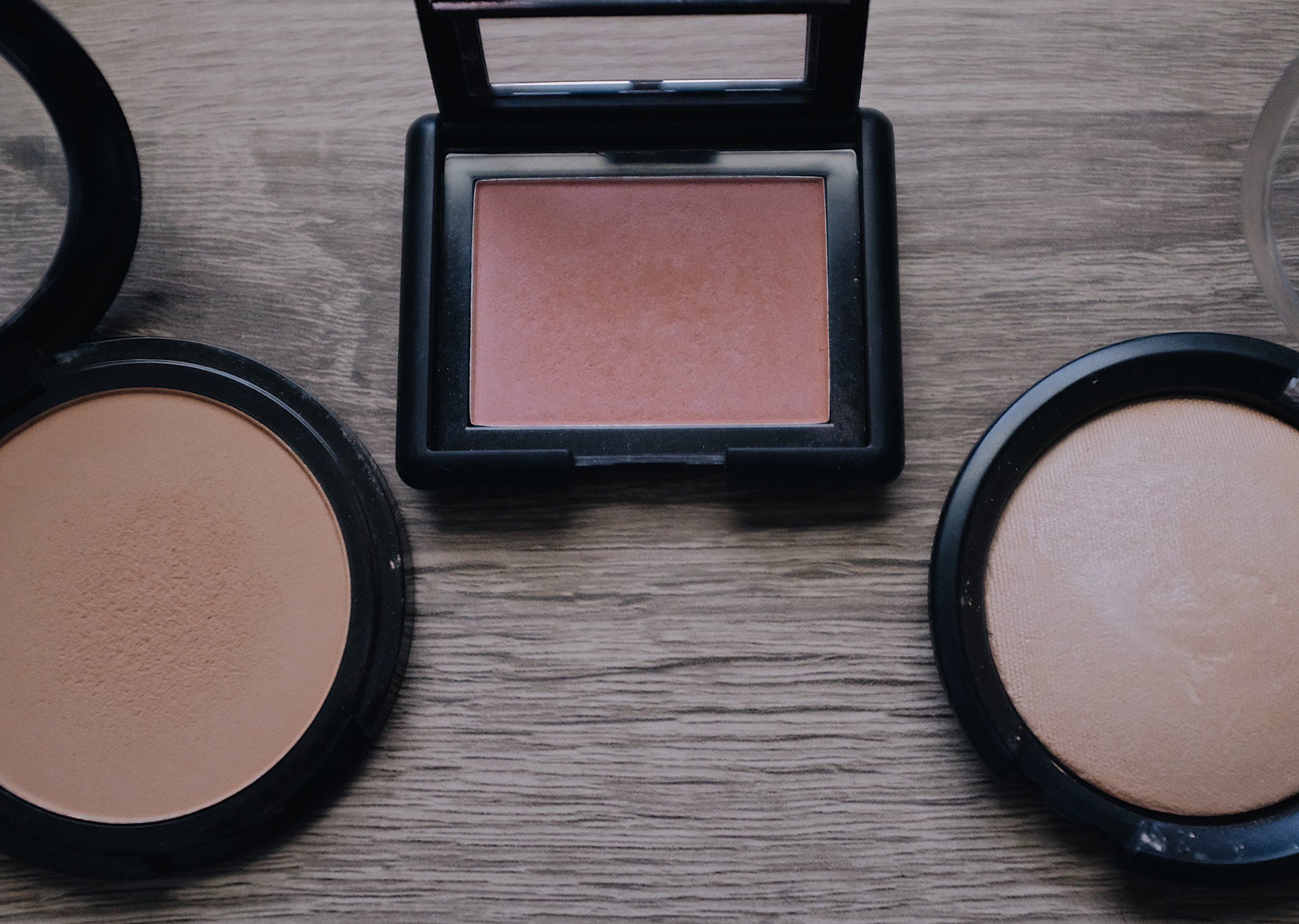 """Face Powders  (from left to right)   ELF 'Primer-Infused Bronzer' in Forever Sunkissed- $6  (for bronzer & crease color on the lid)   - My newest favorite bronzer! This bronzer has no shimmer and has the perfect amount of warmth for my skin tone without making me look muddy or orange.    ELF Blush in Mellow Mauve- $3    -This blush gives that nice """"flushed"""" look with a slight iridescent sheen to it, so it's not flat. Don't worry, it's not glittery or shiny and doesn't clash with highlighter.    Essence 'Pure Nude' Highlighter in Be My Highlight- $4.49    - This highlighter is perfect for the subtle """"lit within"""" glow. It doesn't exaggerate texture on the cheeks either, so it's becomes one with the skin."""