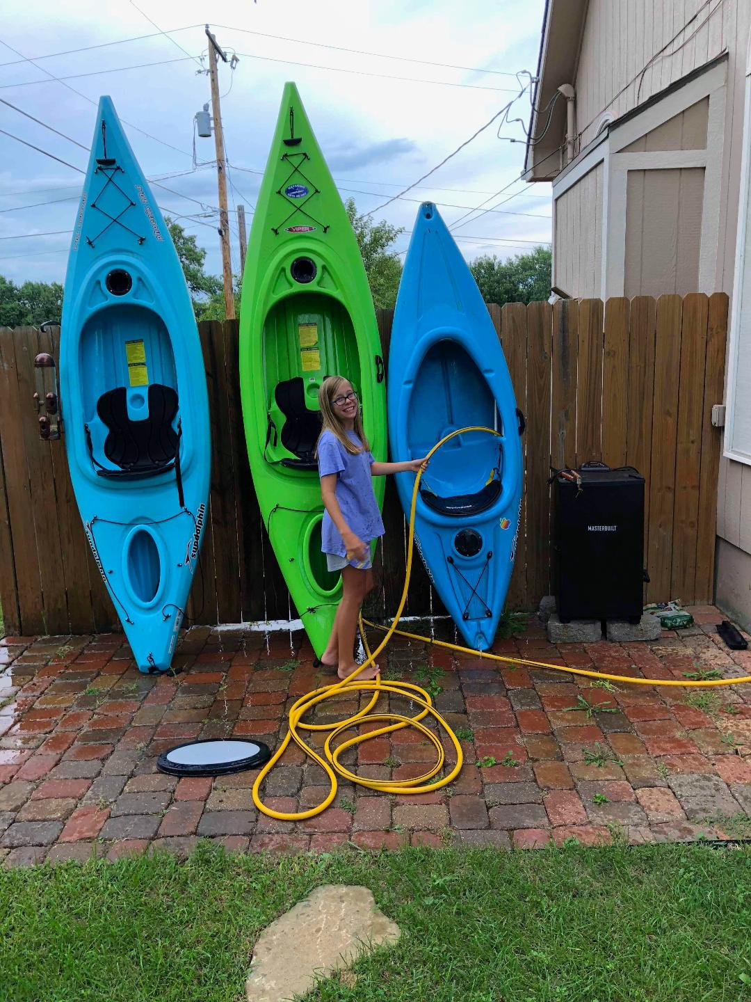 Maddie cleaning the sand and mud off the kayaks.