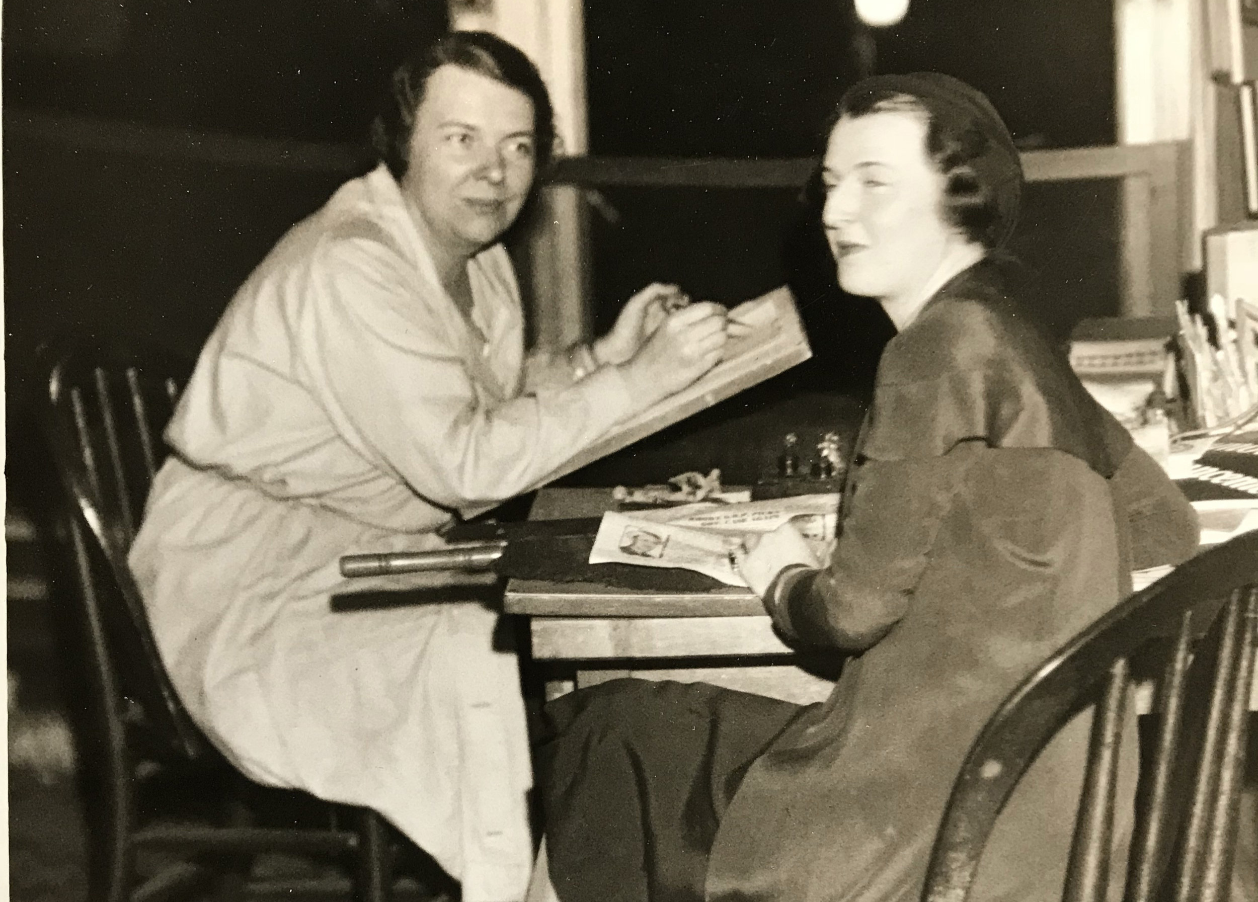 Edith Stevens (left) at her Boston Post drawing table. Circa 1930s
