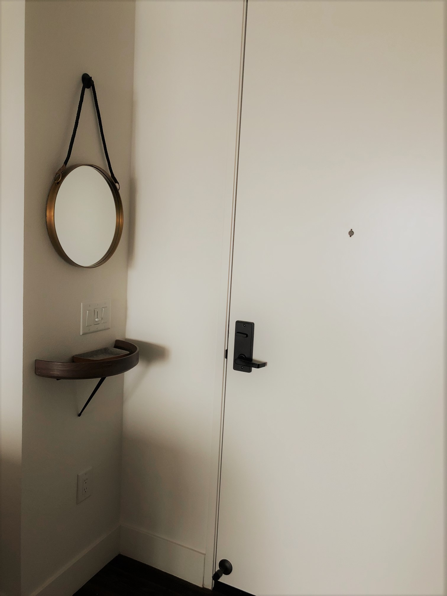"In our minimalist entryway, we have less than two square feet. We've opted for a wall-mounted ""shelf"" to house keys and wallet and the occasional piece of outgoing mail. A mirror replaced a clock as it not only brought light into the dark corner, it saved us from embarrassment more than once."