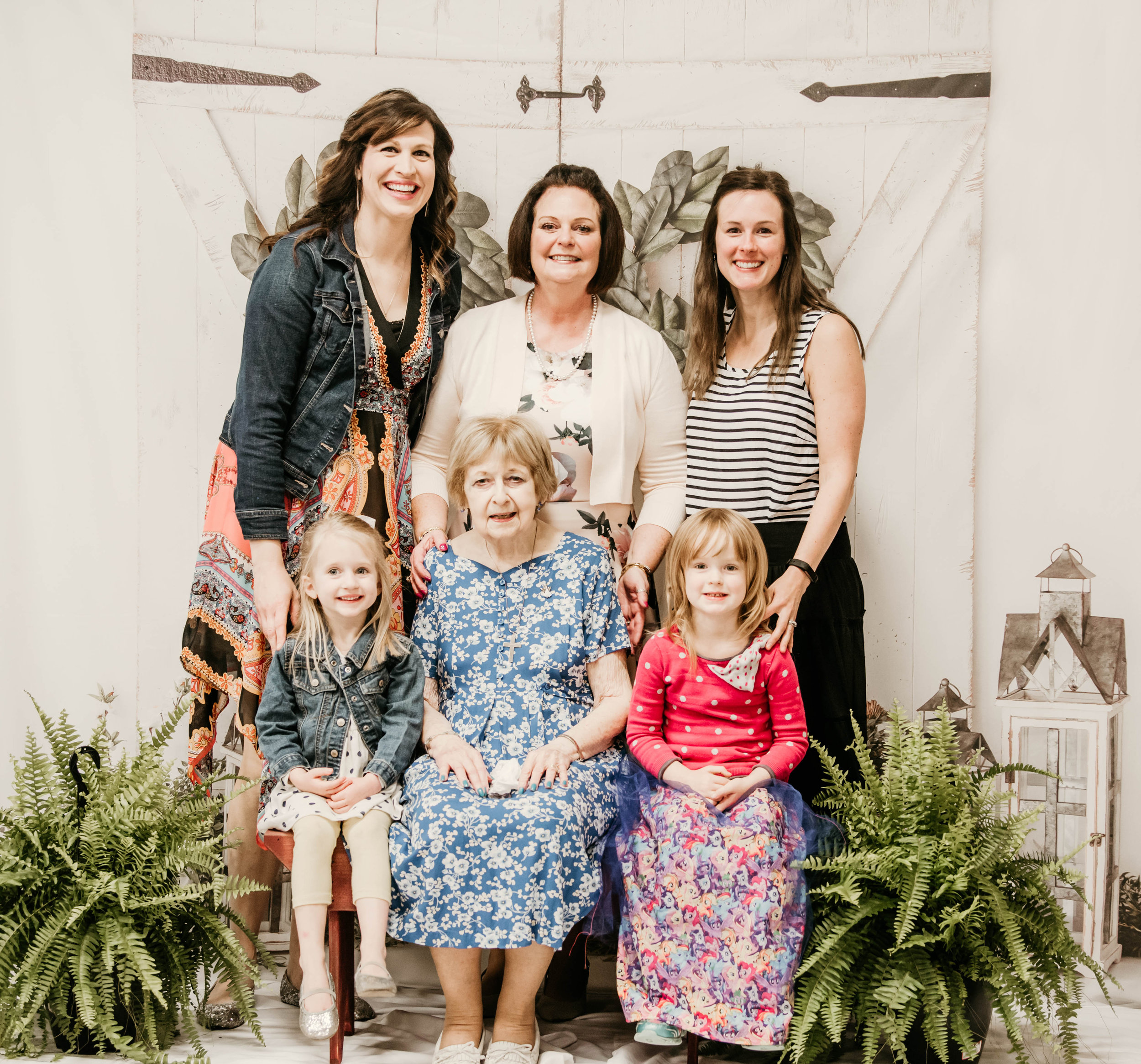 The setup I had for the event. Linda with her mom, daughter-in-laws, and granddaughters.  Thank you Linda for adding the ferns and providing the bench and white sheets.