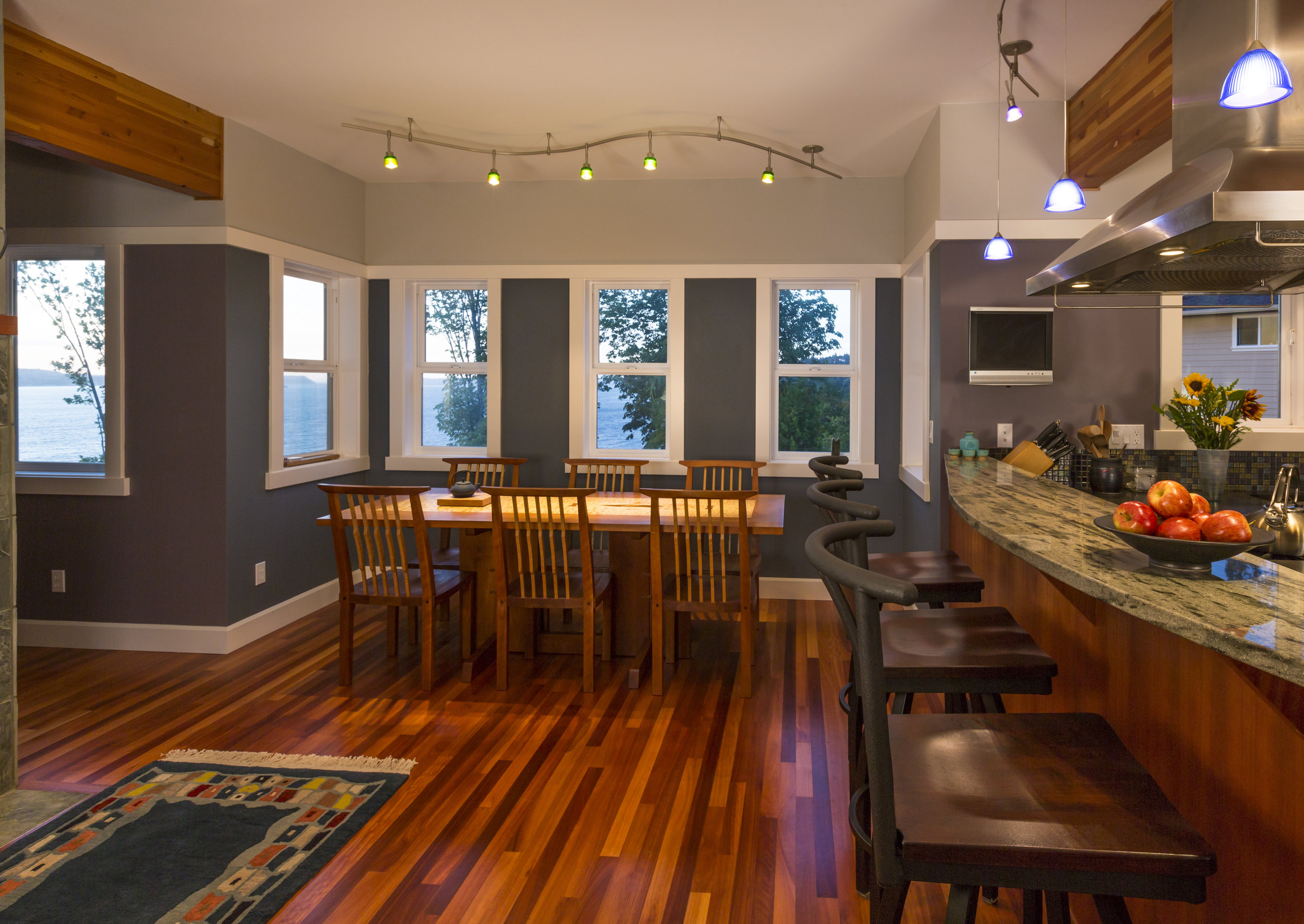 Kitchen breakfast bar and dining area table and chairs with wood floors, granite countertops, accent lighting and view windows in contemporary upscale home interior