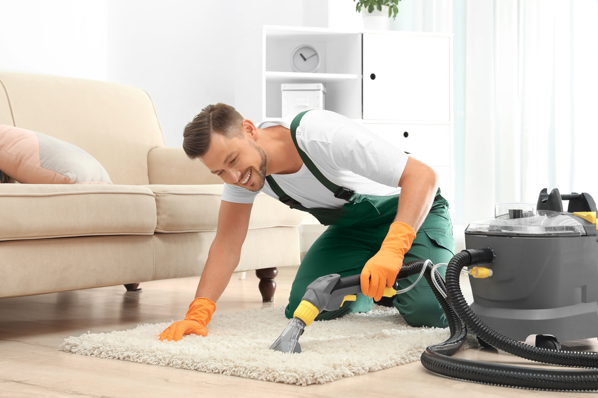 Male janitor removing dirt from rug with carpet cleaner in room
