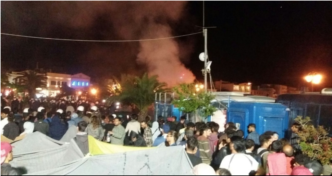 Ultranationalists fill a bin with kerosene, light it and push it at demonstrating refugees and aid workers. Numerous witnesses claimed the police helped attackers pile flammable material into the bins (unverified).