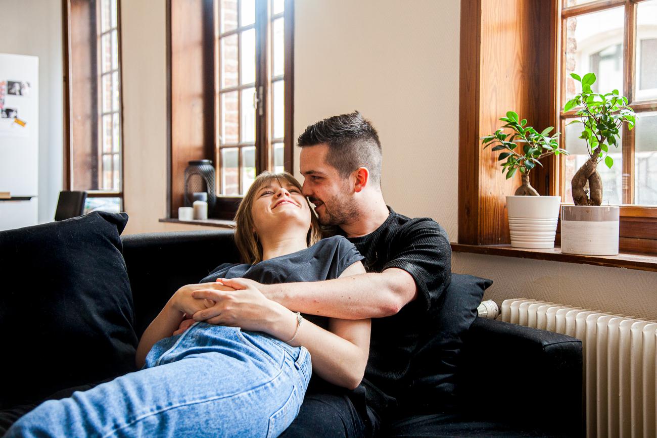 couple riant dans le canapé pendant une séance photo couple à domicile à lille.jpg