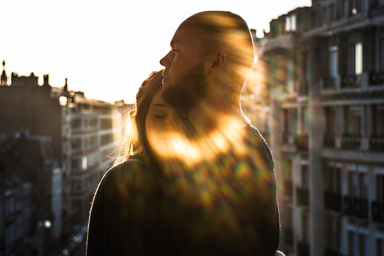 rayons du soleil couchant sur un couple s'enlaçant sur un balcon pendant une séance photo couple à domicile d'1h, à lille.jpg