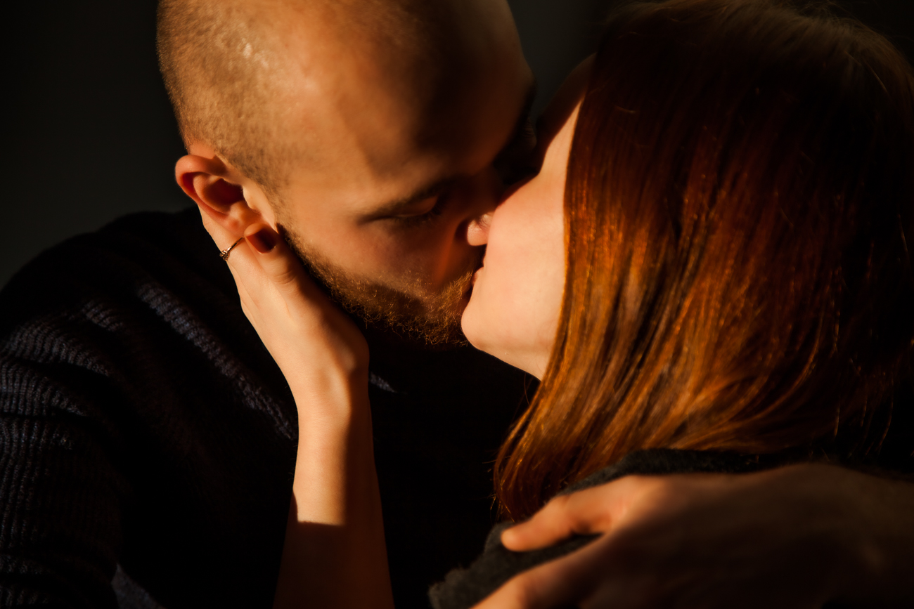 plan sérré d'un baiser de couple dans la chambre pendant une séance photo couple à domicile à lille centre.jpg