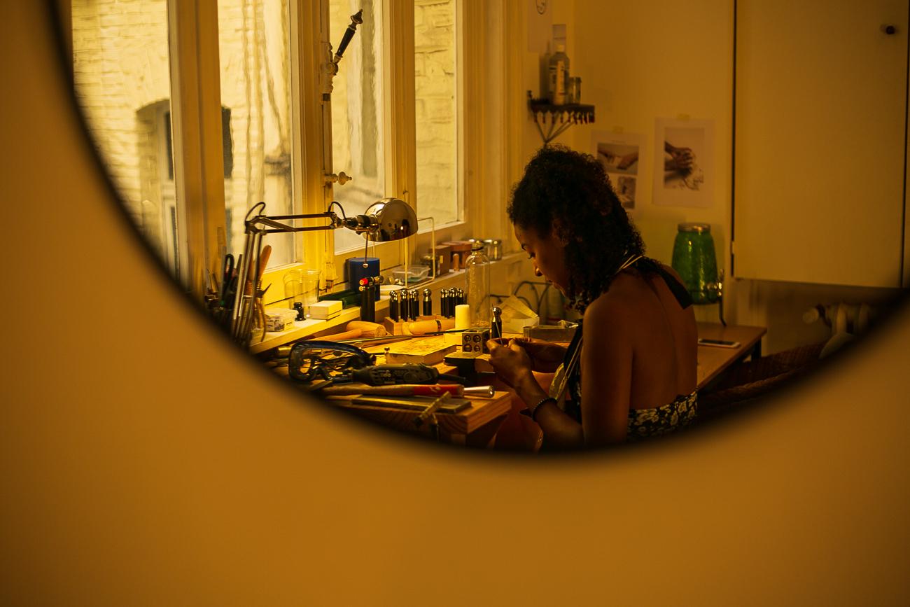 photo à travers un mirroir d'une creatrice de bijoux lilloise au travail- Atelier Armoure - prestation pour les professionnels séance photo portrait artisan.jpg