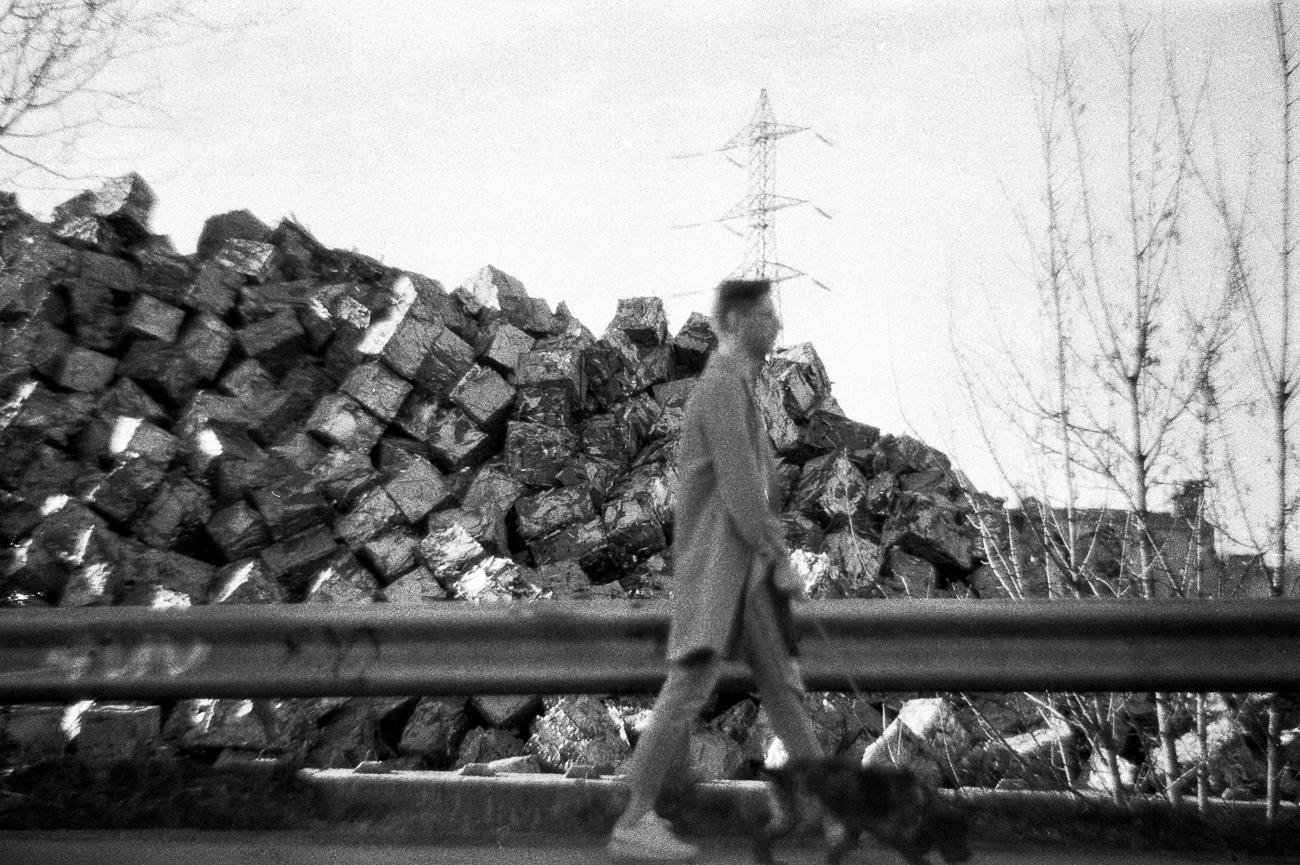 photo fine art argentique en noir et blanc projet mémoire de rêvelise rohart - homme promenant son chien devant un amas de ferraille.jpg.jpg