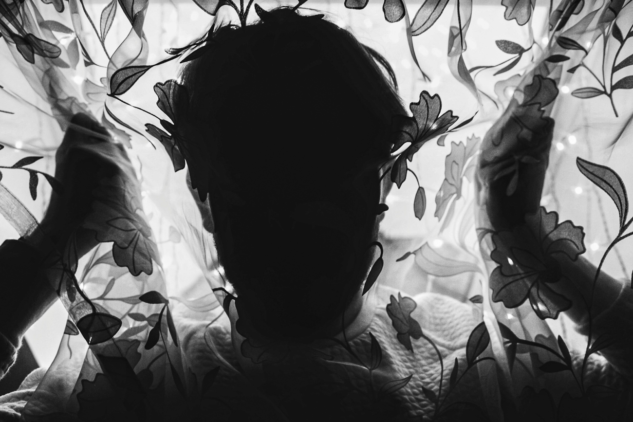 photo fine art projet mémoire de rêvelise rohart -silouhette d'un jeune homme dans un rideau fleuri.jpg