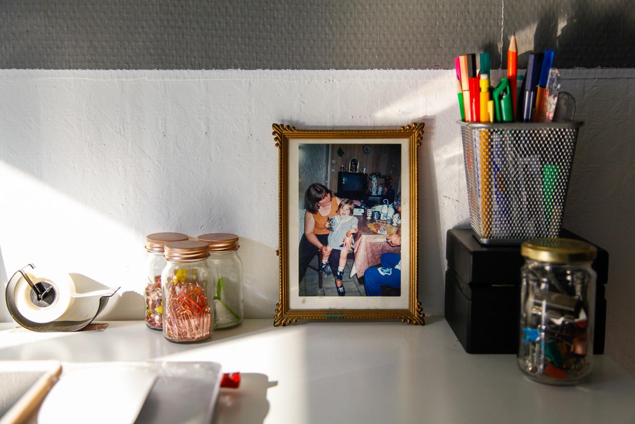objets sur le bureau avec au centre, la photo d'une petite fille sur les genoux de sa mère - photo couleur fineart projet photo choses à soi de rêvelise rohart - série lise rêvée.jpg