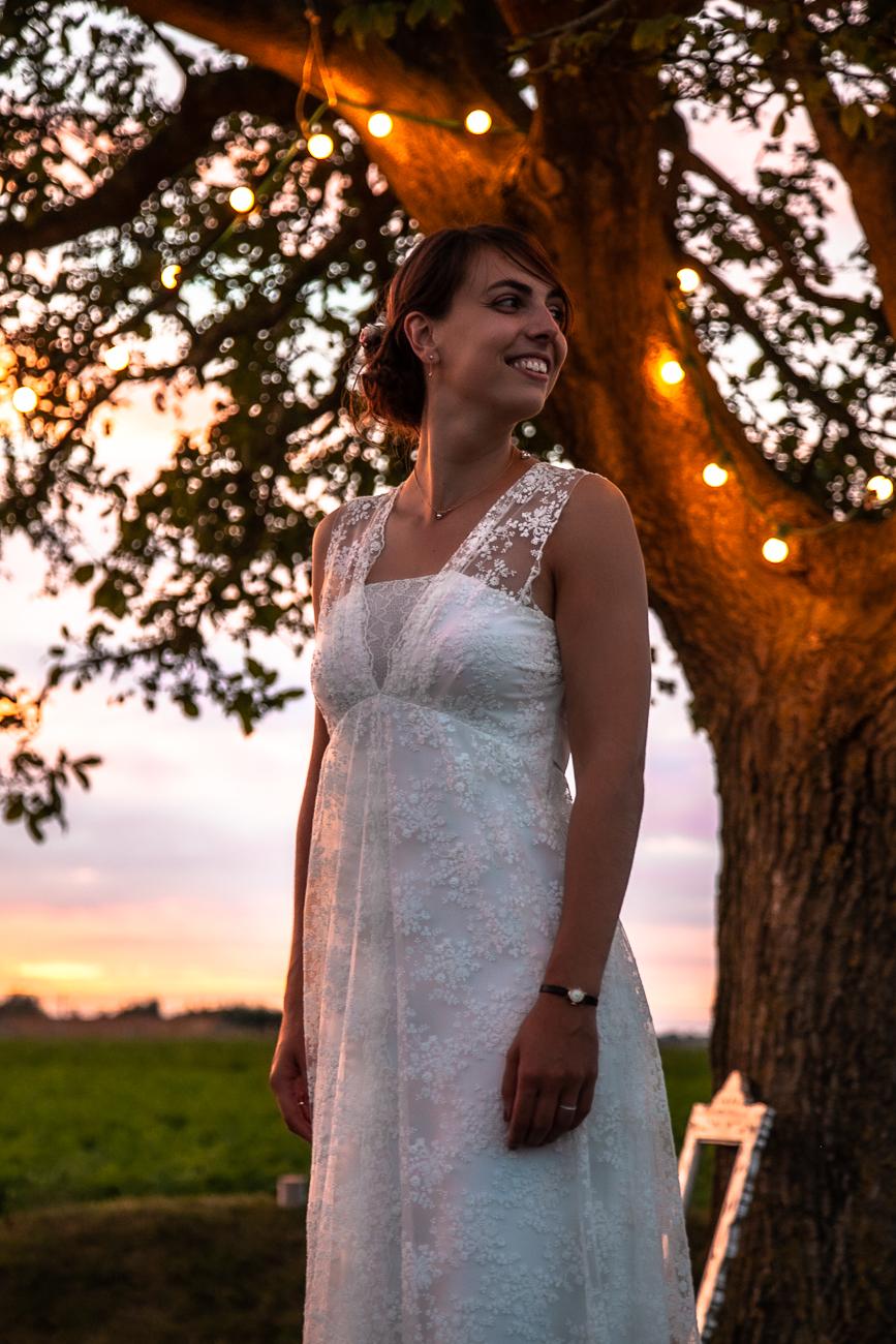 jeune mariée souriante dans le jardin à la tombée de la nuit le jour de son mariage - © rêvelise rohart pendant un reportage mariage dans le nord et la belgique.jpg