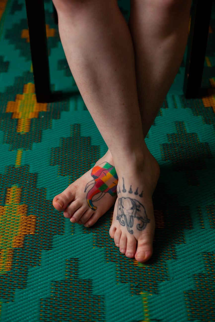 pieds tatoués d'une femme en body noir pendant une séance photo boudoir à domicile à lille (59).jpg