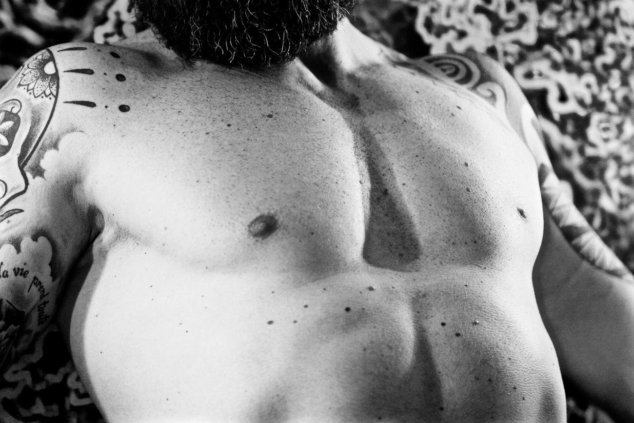 photo noir et blanc détail peau homme très musclè nu dans une chambre d'hotel pendant une séance boudoir à lille (59).jpg