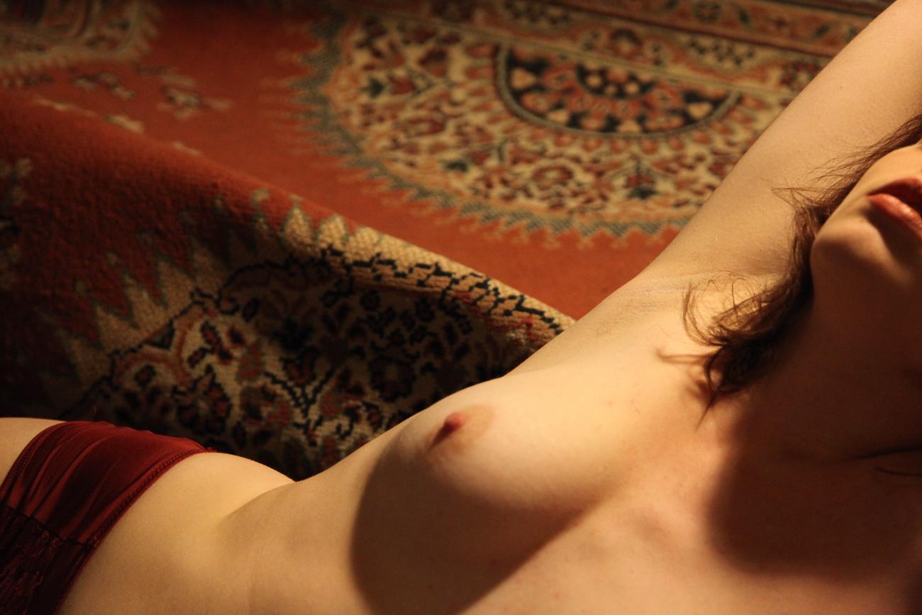 photo jeune femme nue allongée sur un tapis dans une lumière chaude pendant une le séance photo boudoir à roubaix (59).jpg