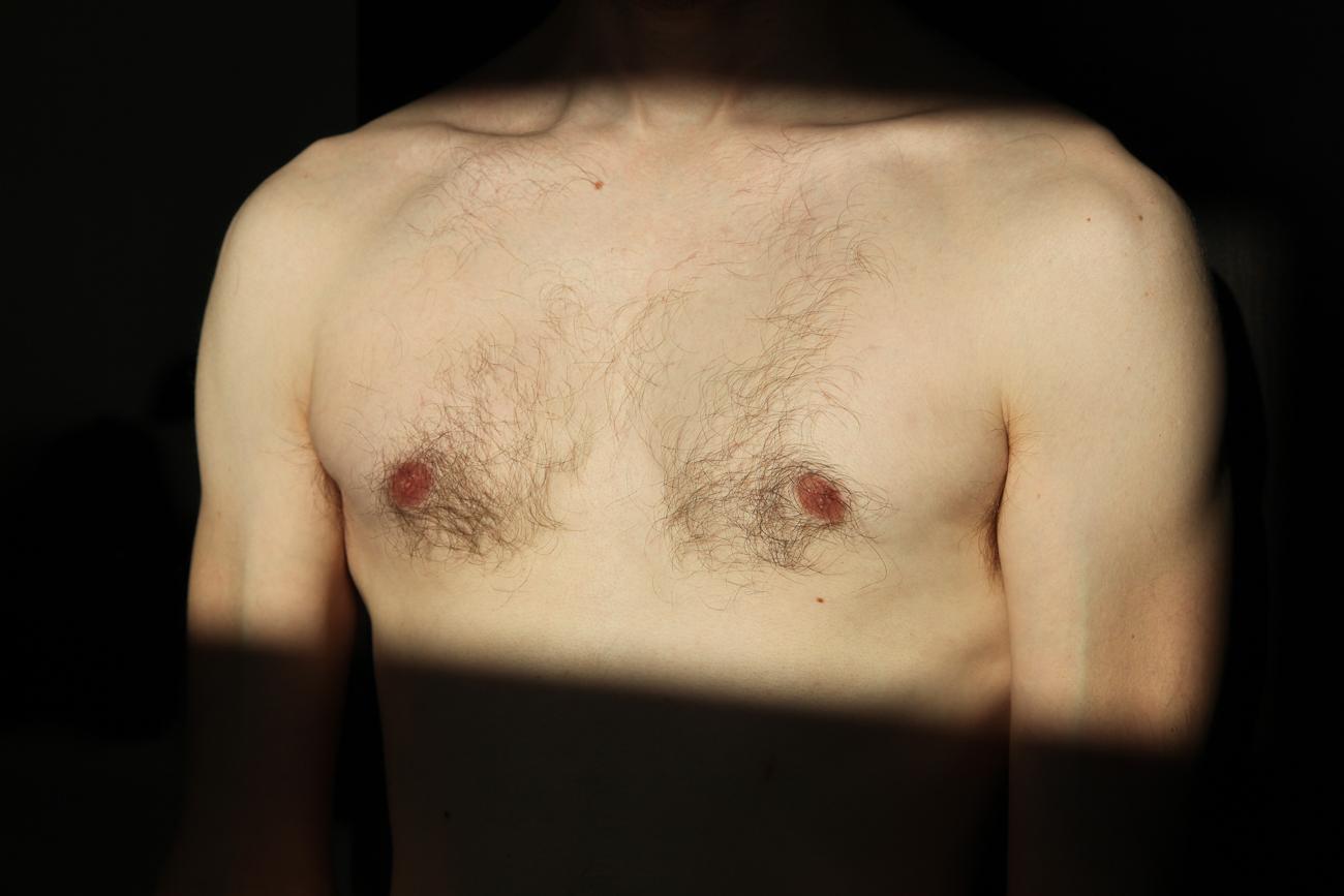 photo détail du torse d'un homme dans la lumière pendant séance photo boudoir à lille (59).jpg