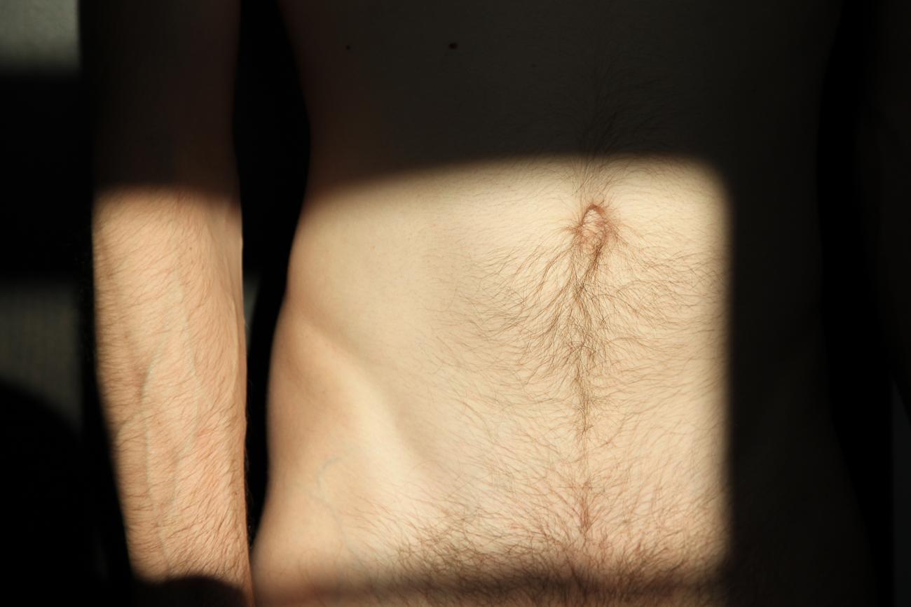 photo détail du bas ventre d'un homme dans la lumière pendant séance photo boudoir à lille (59).jpg