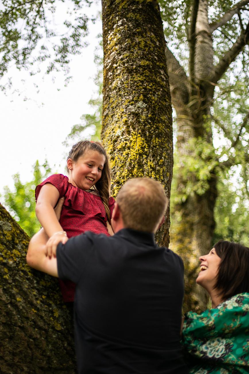 des parents aident une petite fille à grimper dans un arbre pendant un reportage photo famille dans le nord-pas-de-calais à douvrin (62).jpg