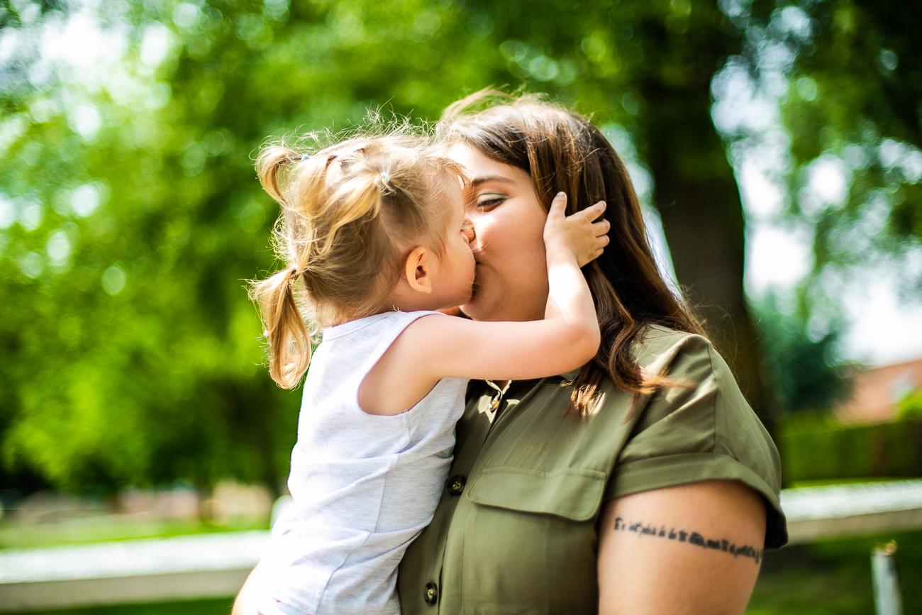 petite fille embrasse sa maman pendant un reportage photo famille dans le nord-pas-de-calais à douvrin (62).jpg