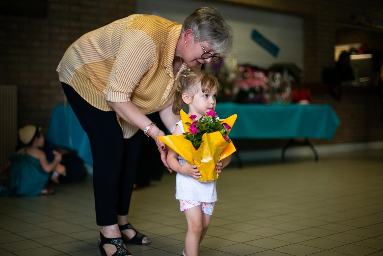 petite fille encouragée par une femme à aller remettre des fleurs à sa grand-mère pendant un reportage photo famille dans le nord-pas-de-calais à douvrin (62).jpg