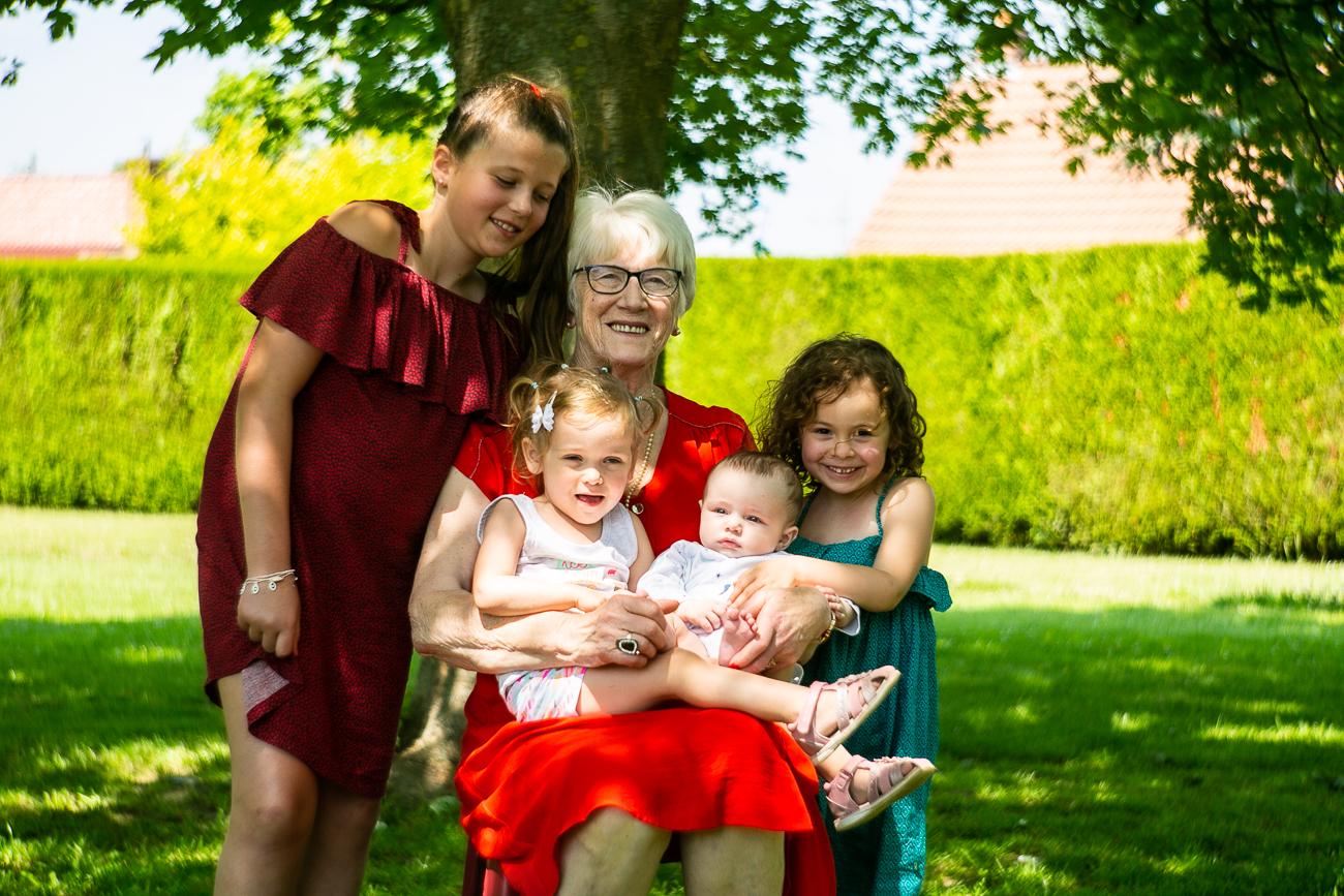 grand-mère en robe rouge vif avec ses petits-enfants pendant un reportage photo famille dans le pas-de-calais à douvrin (62).jpg