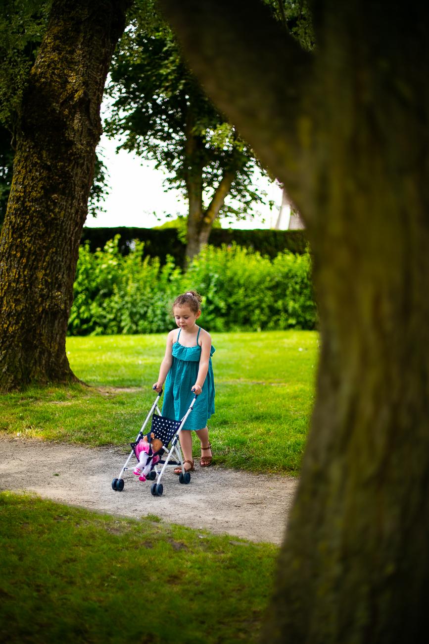 petite fille dans un parc avec une poussette pendant un reportage photo famille dans le pas-de-calais à douvrin (62).jpg