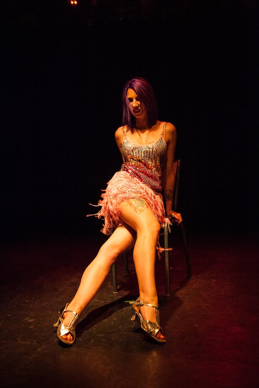 femme aux cheveux violets danse jambes croisés sur une chaise sur scène pendant son numéro -photoreportage spectacle burlesque à lille de l'association wonder burle'school à la barraca zem.jpg