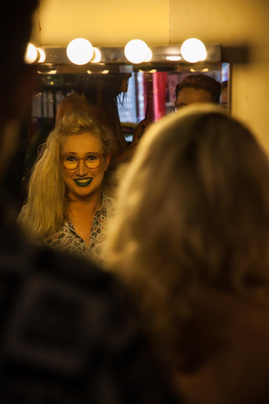 sourire amusé dans le miroir pendant la préparation des danseuses -photoreportage spectacle burlesque à lille de l'association wonder burle'school.jpg