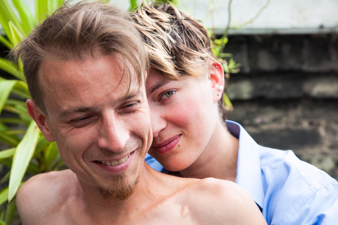 jeune femme magnifique enlace son bien aimé souriant sur la terasse de leur appartement pendant une séance photo couple à lille (59) © revelise rohart.jpg