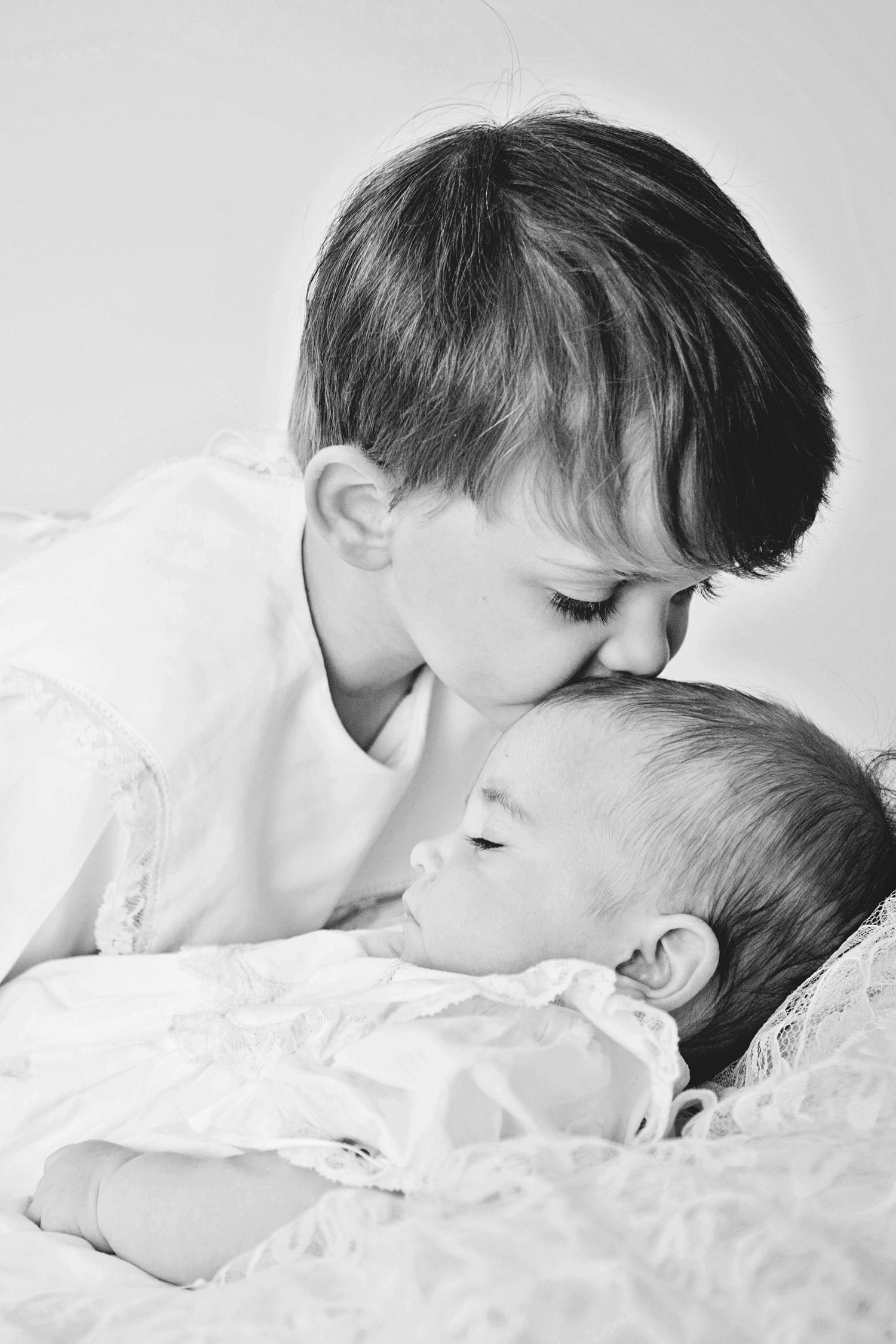 newborn-sibling-kiss.jpg