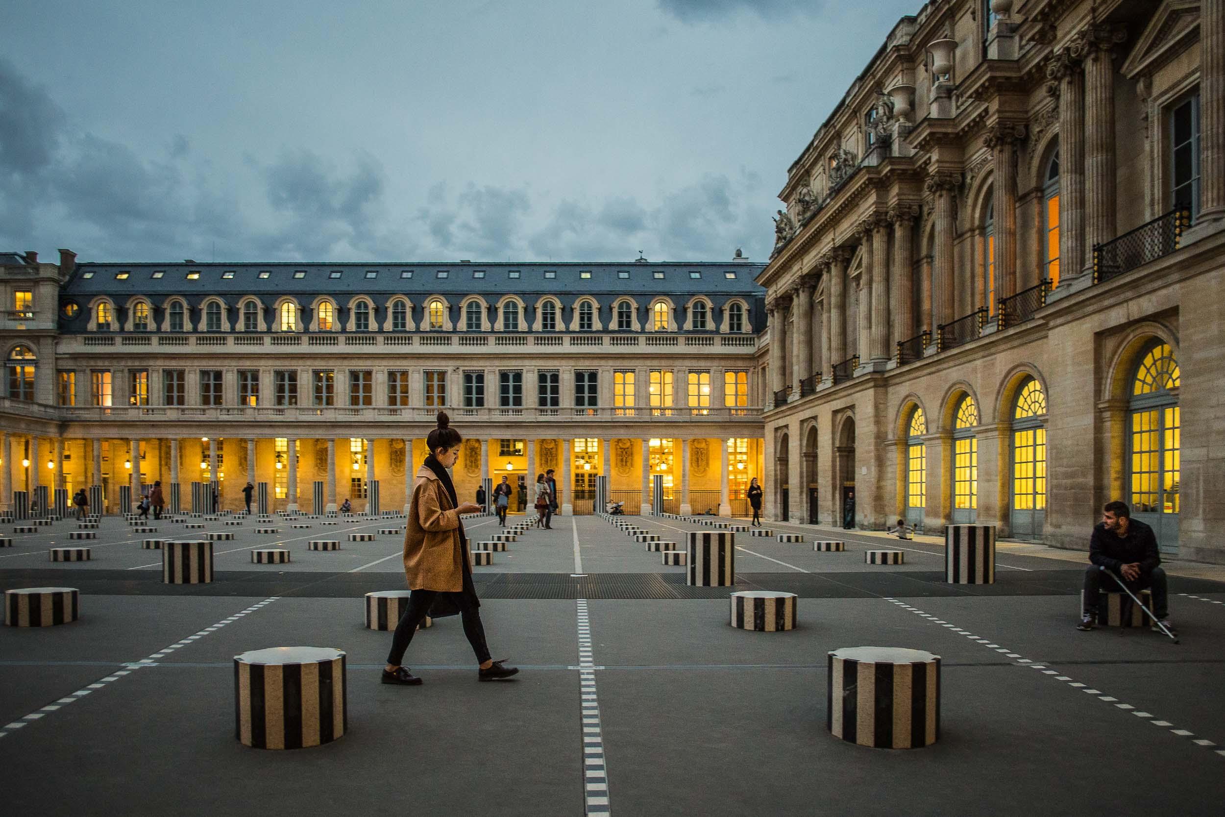 Paris-Palais-Royal-Woman-Walking-Man-Sitting.jpg