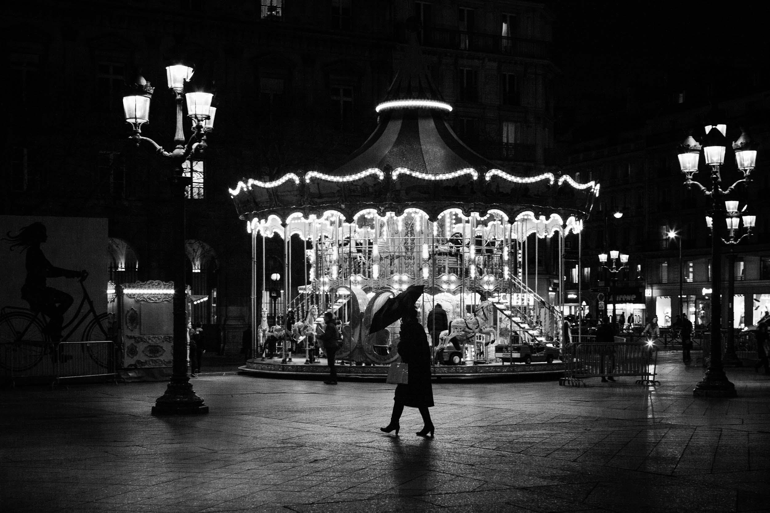 Paris-woman-walking-with-umbrella-front-of-carousel.jpg